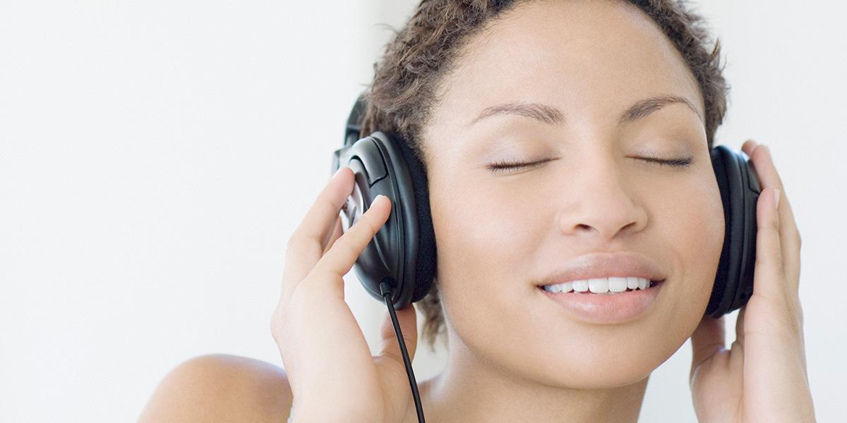Visage d'une jeune femme, qui yeux fermés et souriante, tient des écouteurs contre ses oreilles
