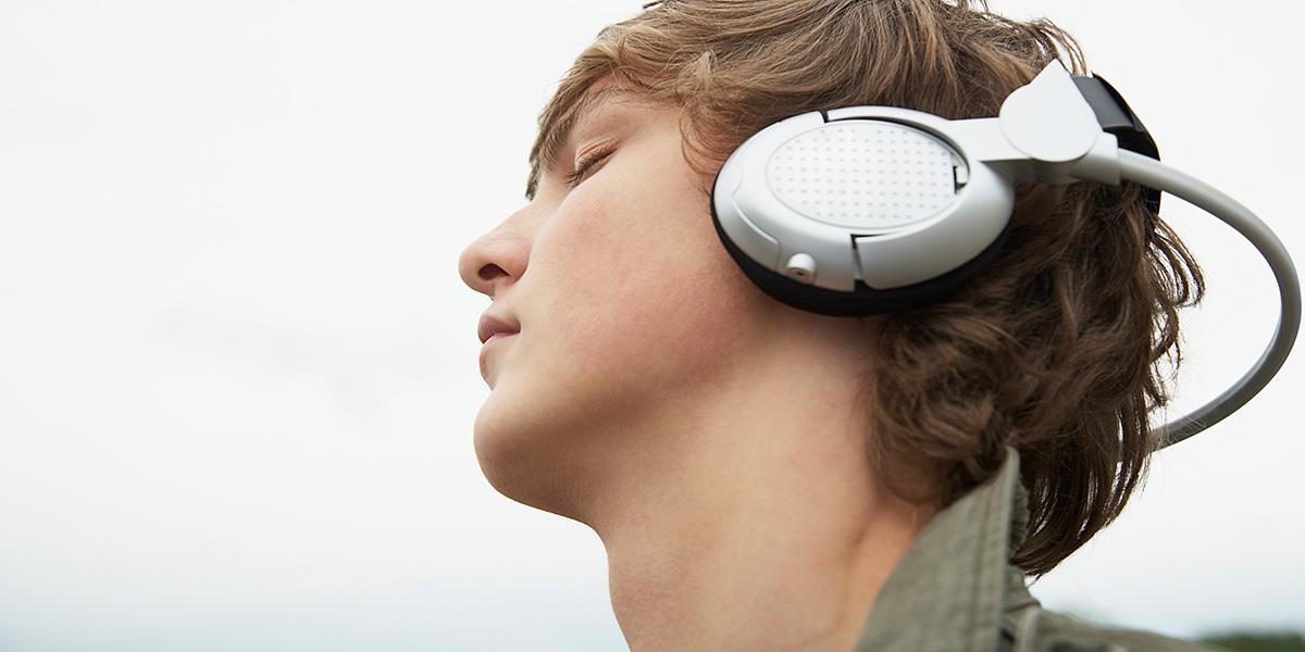 Visage d'un adolescent, yeux fermés, avec de gros écouteurs aux oreilles