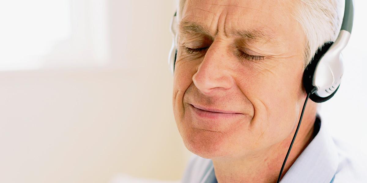 Visage d'un homme, yeux fermés, qui écoute paisiblement avec des écouteurs