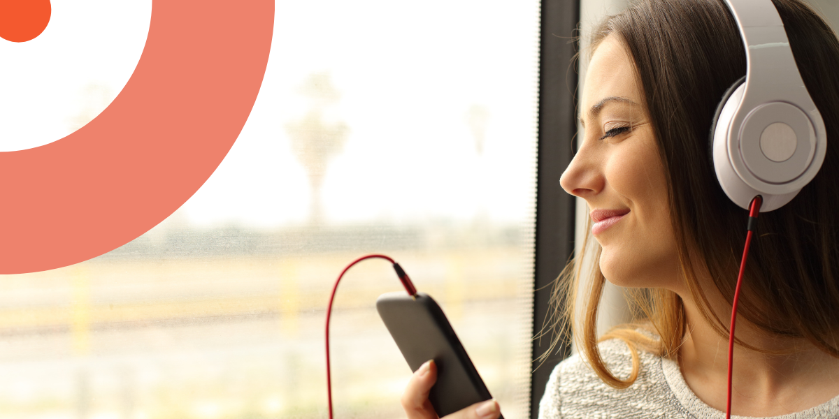 Une femme écoute son livre audio dans le train les yeux fermés.