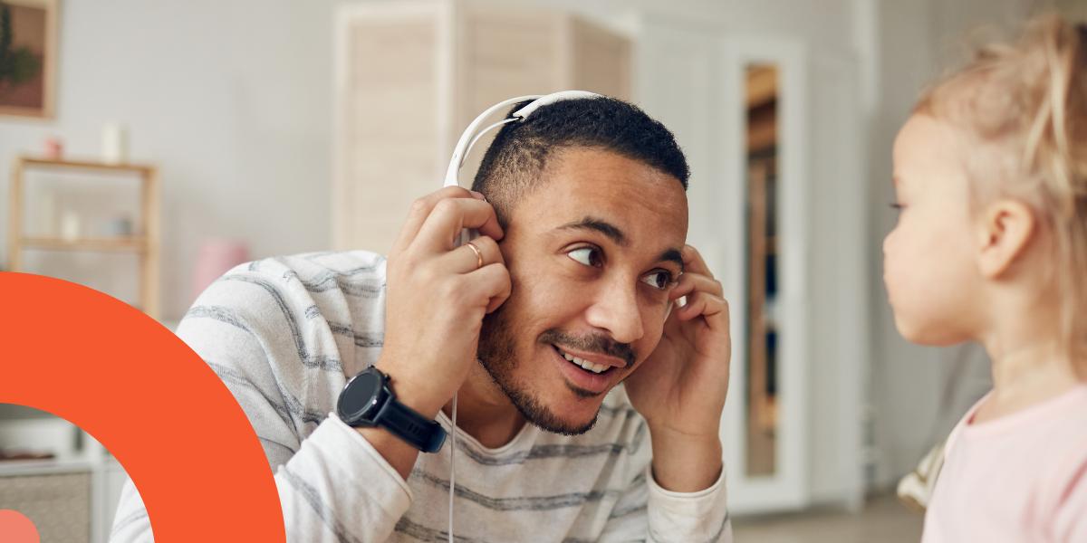 Un homme se penche vers une fillette pour lui prêter sa pair d'écouteur et lui faire entendre l'histoire.
